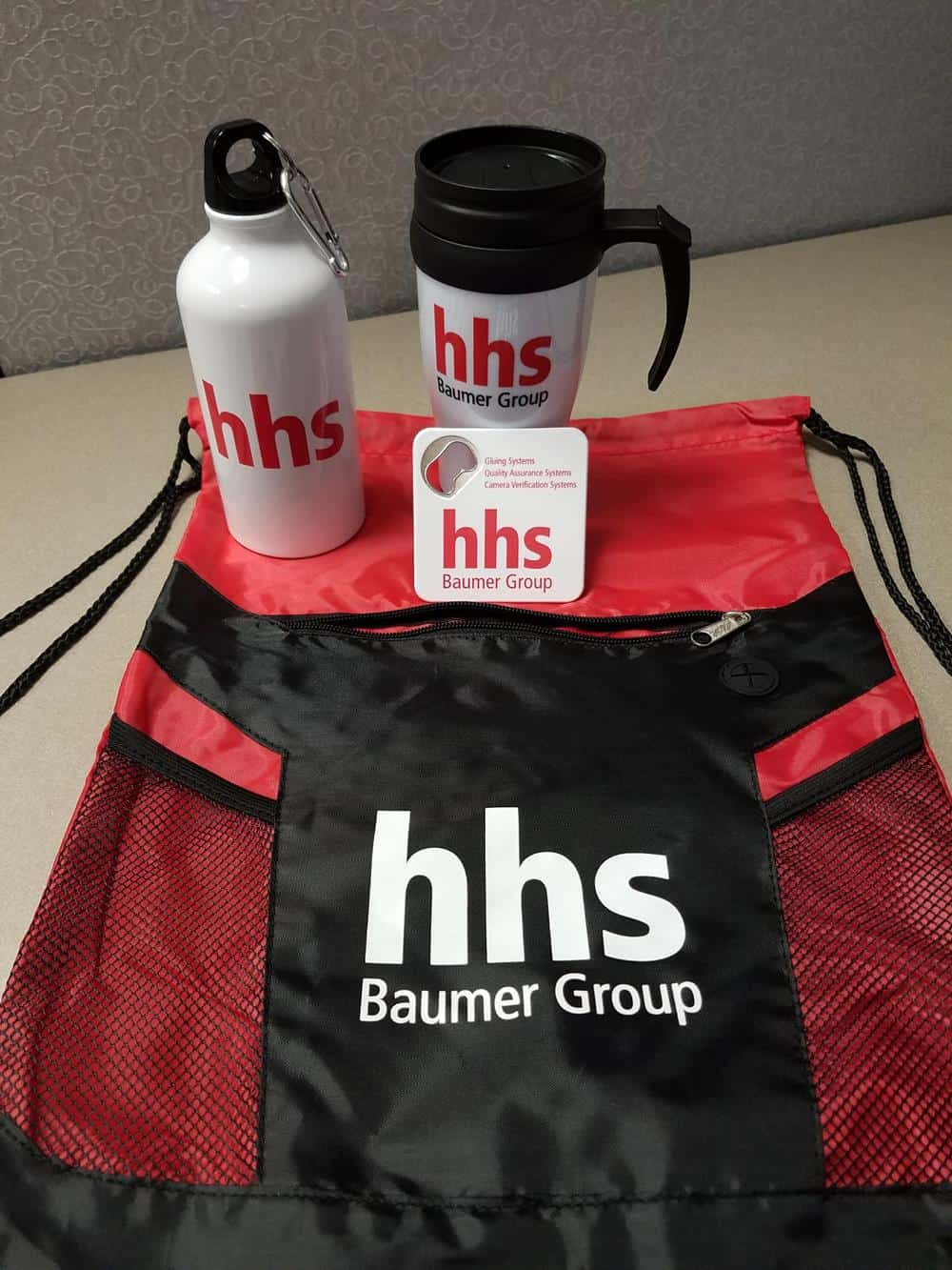 Red and black drawstring sports bag with a metal sports bottle and travel tumbler