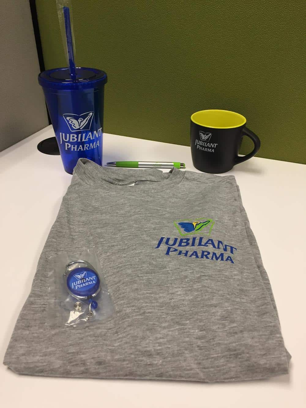 T-shirt, coffee mug, pen, badge holder and plastic tumbler with straw