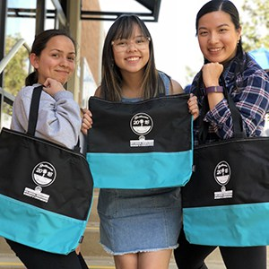 Three women posing for the camera holding their black and teal swag bags