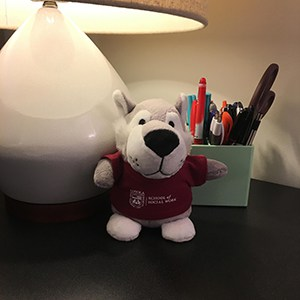 A wolf Bean Bag Buddy sitting on a desk with a lamp and pens in a holder.