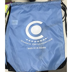 Empty blue drawstring bag branded to Chance Orthodontics