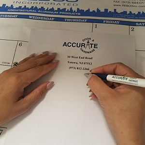 Hand holding a pen next to paper