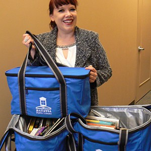 A woman holds blue Utility 36-Can Cooler Totes.