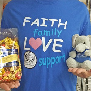 A woman in a blue shirt holds a bag of popcorn and a stuffed elephant with logo.