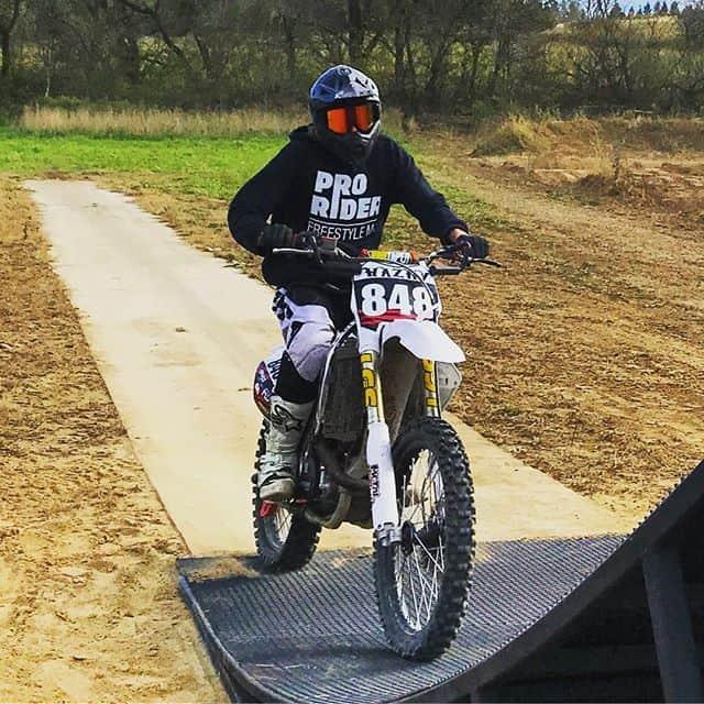 Motocross rider on bike, wearing promotional hoodie