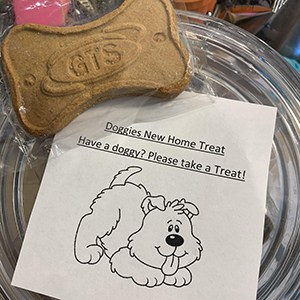 Doggie treat next to a giveaway paper asking people to take a treat