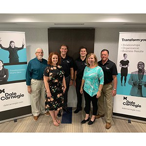 Group of staff posing next to two full-size banner ads