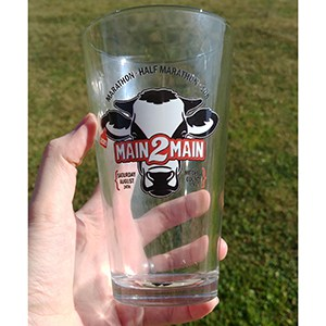 Hand holding branded pint glass, with a background of green grass