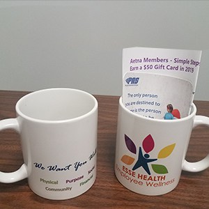 Two white branded mugs, with promo brochures inside one mug