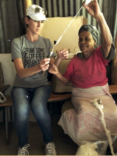 Woman showing other woman how to hand spin thread