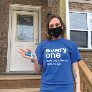 Woman on front steps of house holding Habitat for Humanity keychain.