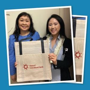 Two Hawai'i Cord Blood Bank staff displaying a branded reusable grocery bag.