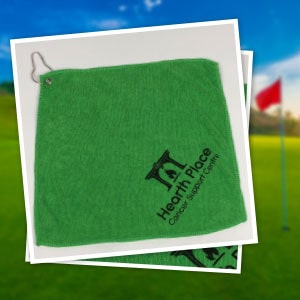 Hearth Place Cancer Support Centre branded golf towel with a golf course in the background.