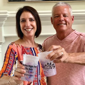 Two adults clinking their branded cups together.