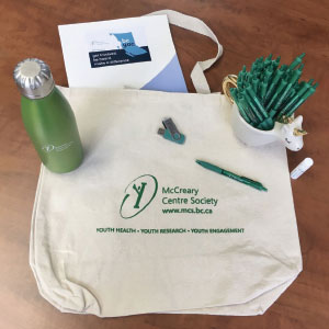 Promotional tote bag, water bottle, USB drive, lip balm and a cup of pens.