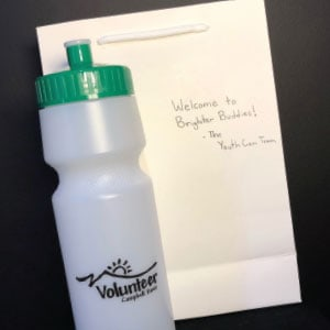 "A promotional water bottle and note that says, ""Welcome to Brighter Buddies."""