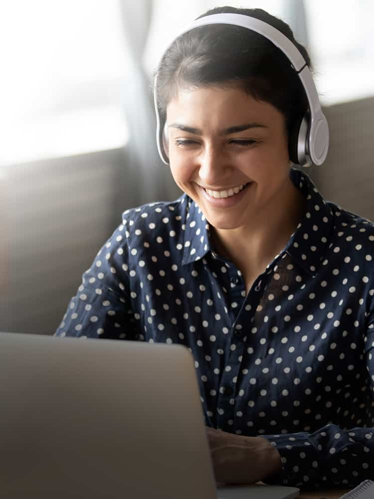 A woman watching something on a laptop with headphones.