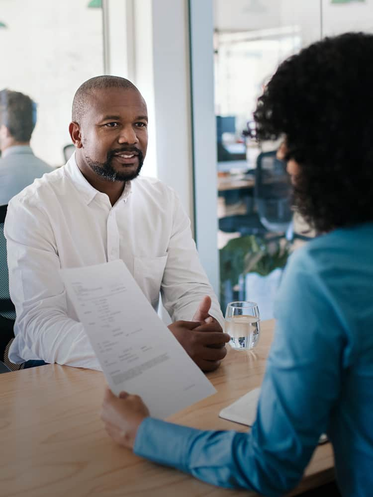 Woman interviewing a man while looking at his resume