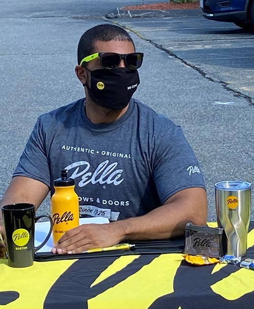 A Pella employee with a table full of promotional items
