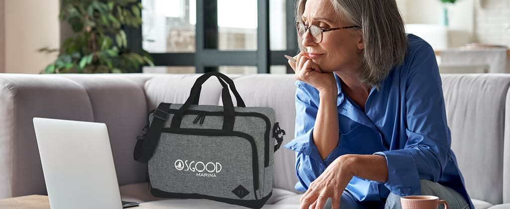 A woman working on a laptop next to a branded messenger bag