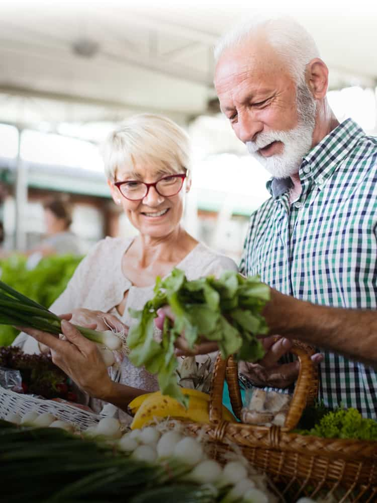 husband and wife looking at vegetables at farmers market