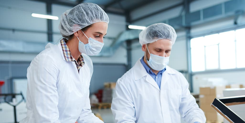 two food workers wearing hair nets and face masks in factory