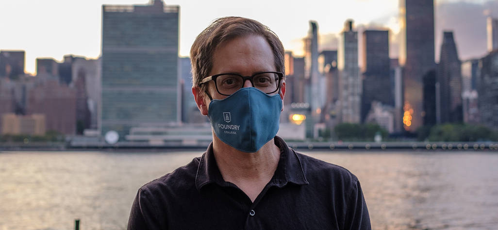 CEO and President of Foundry College wearing a branded facemask with city scape behind him