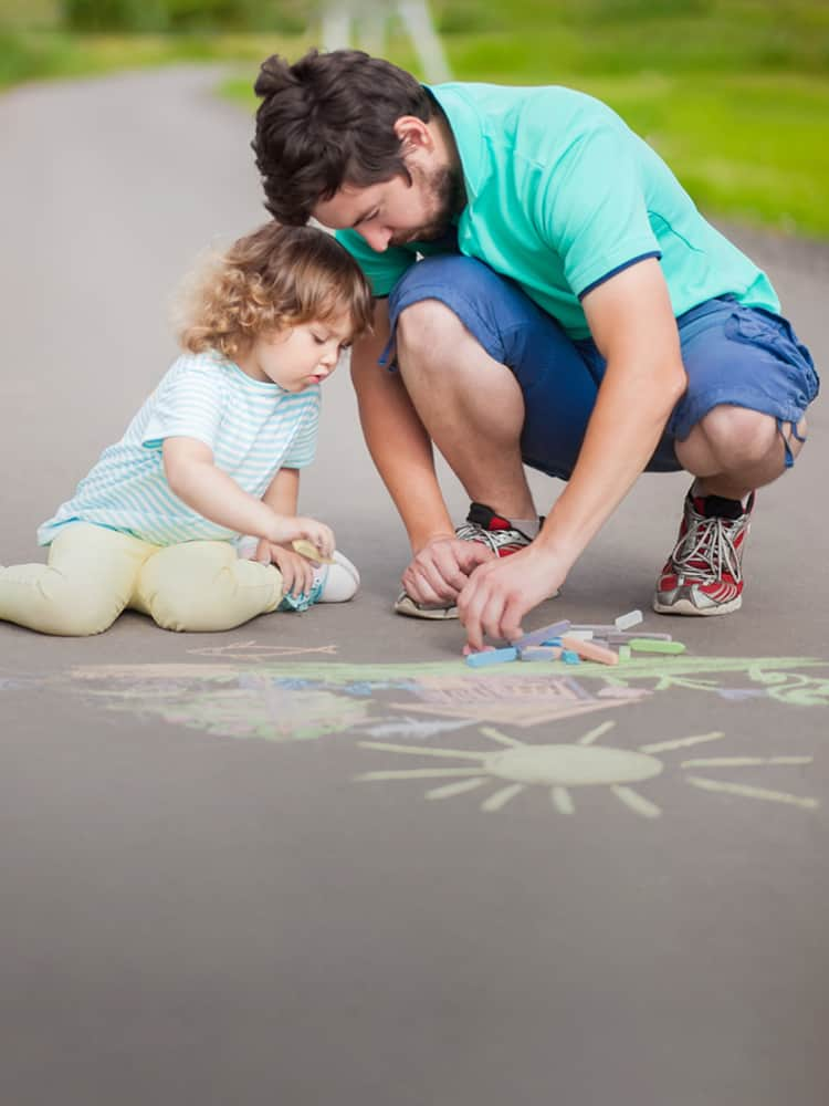 Father and daughter playing with sidewalk chalk.