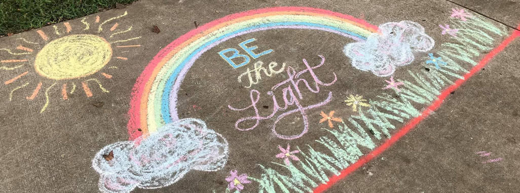 Chalk artwork design of rainbow and sun with words - Be the Light