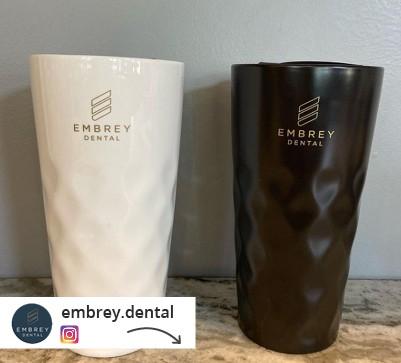 white and black branded travel mugs