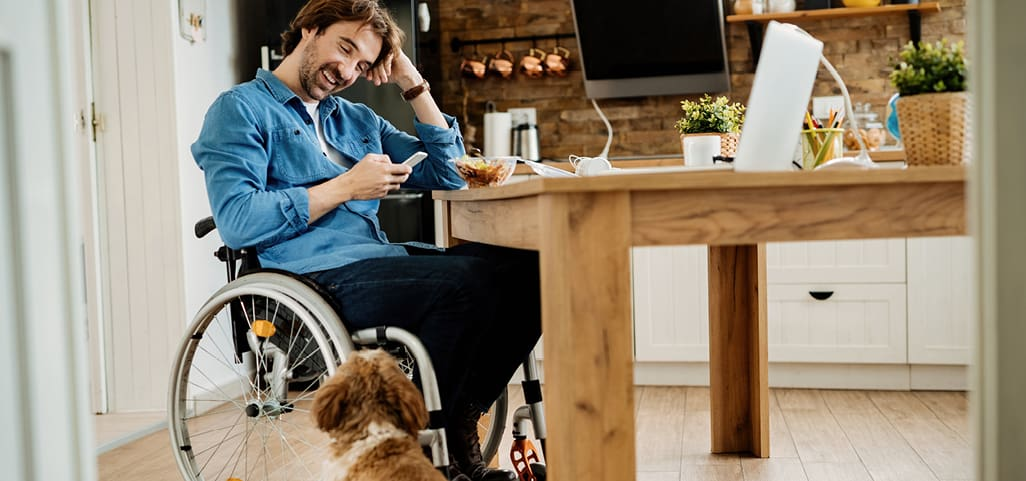 Man in wheelchair at kitchen table looking at cell phone