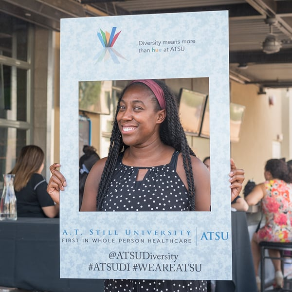 African-American Woman holding up a sign promoting diversity for ATSU