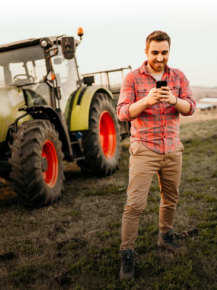 Farmer looking at cell phone with tractor behind him