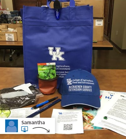 branded bag with contents of bag laying in front - hat, pens, seed packet, etc.