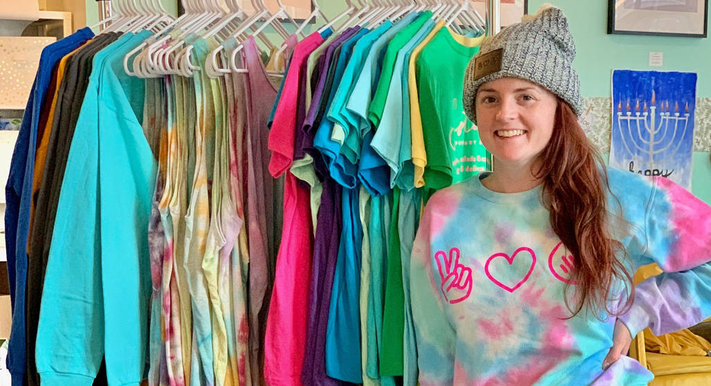 Woman in branded sweatshirt and hat standing next to rack of branded merchandise she is selling