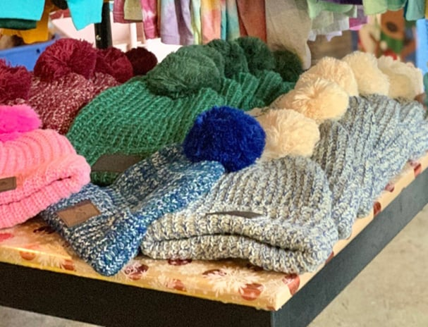 table filled with branded winter hats for sale