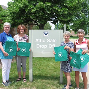Four volunteers holding their green canvas grocery totes, posing by their drop-off sign
