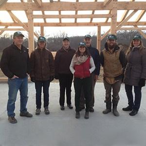 Group of volunteers, wearing green branded hats, posing by wooden barn frame