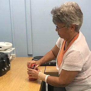 Woman using rubber jar opener to open a jar