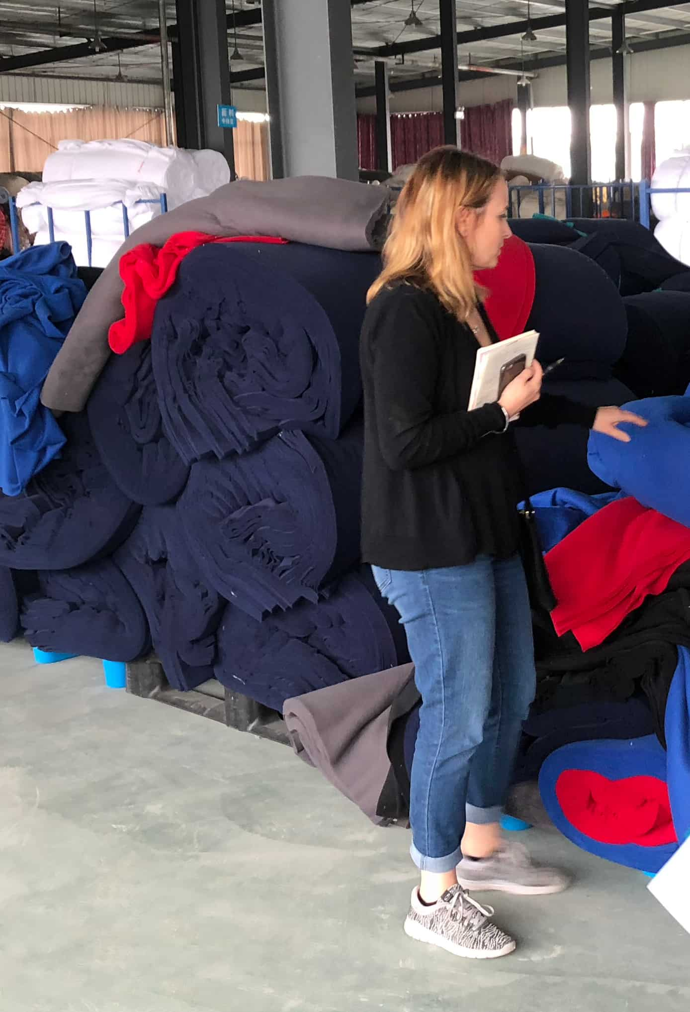 Member of 4imprint's merchandising team reviewing and selecting promotional fleece fabric rolls.