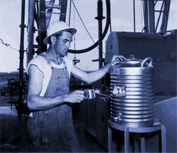 A man takes water from a metal water cooler
