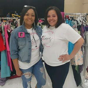 Two volunteers posing in their branded T-shirts, standing in front of clothing racks