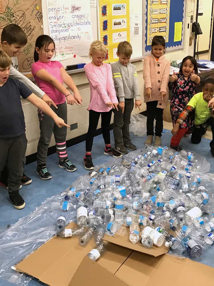 Students standing near a large collection of empty water bottles.
