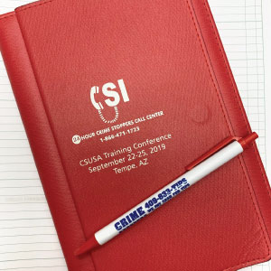 A branded pen and notepad for an article on Crime Stoppers.