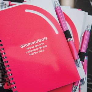 A GlamourGals notebook and pen.