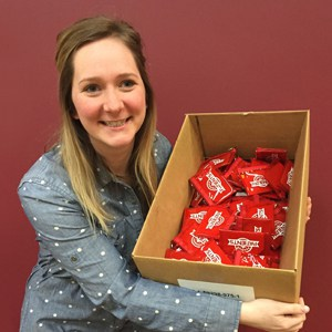 Woman smiling and holding a cardboard box of KitKats in front of a red wall