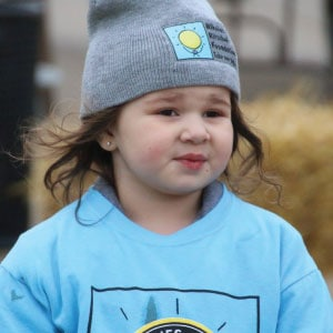 Young child wearing a branded beanie and a blue branded T-shirt