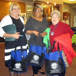 The RSVP volunteers hold custom screen-printed tote bags purchased with a one by one® grant.