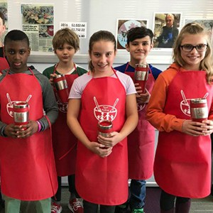 Children at Regina Catholic Schools-École St. Élizabeth showing coffee mugs with logo designed by a student and custom printed aprons.