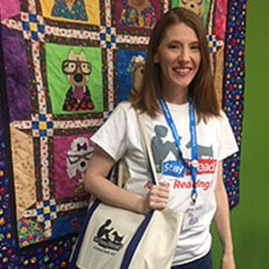 Woman holding canvas bag and smiling in front of a quilt hanging on a green wall